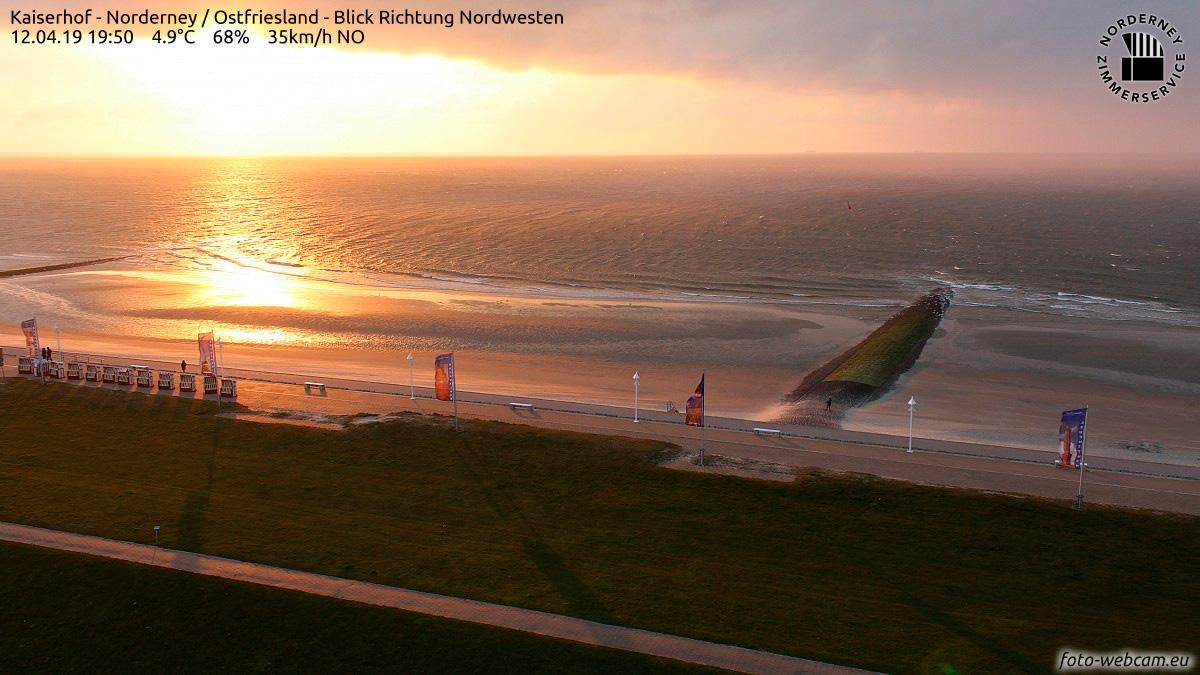 Sonnenuntergang über der Nordsee am 12. April 2019: Im Vordergrund die Strandpromenade von Norderney mit Strandkörben und Fahnen