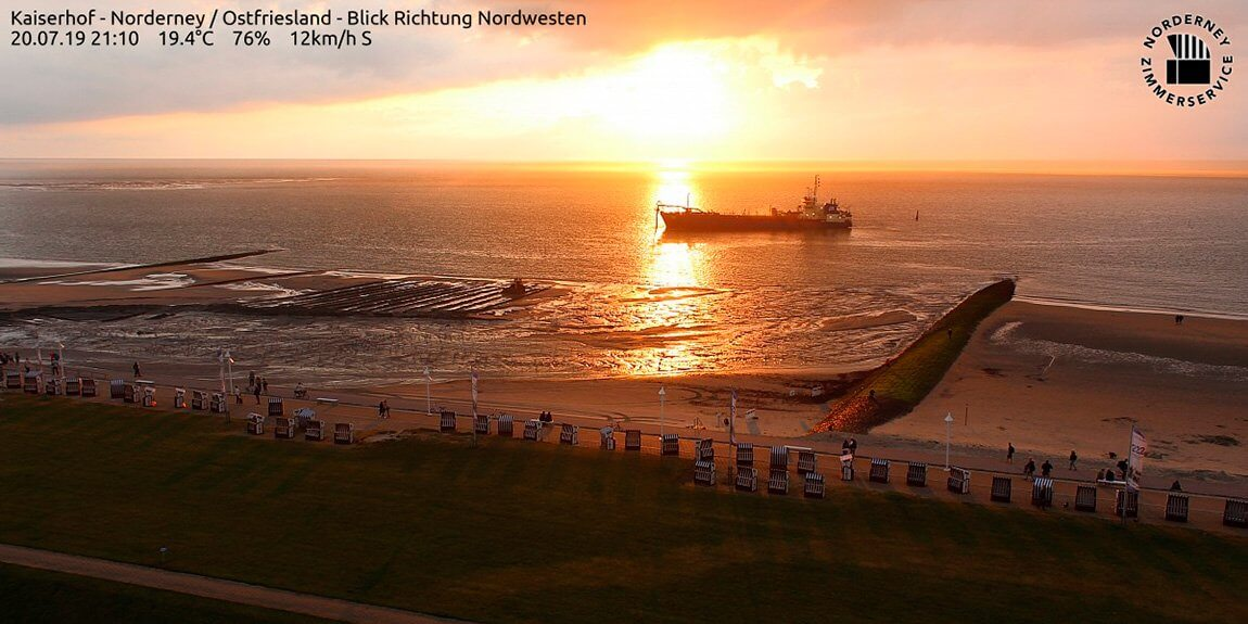 Sonnenuntergang über der Nordsee am 20. Juli 2019: Auf der Nordsee fährt ein Schiff, im Vordergrund die Strandpromenade von Norderney mit Strandkörben und Fahnen und Menschen