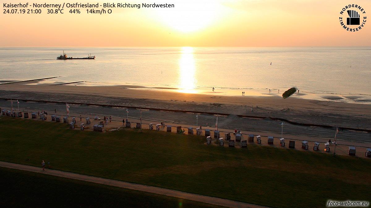 Sonnenuntergang über der Nordsee am 24. Juli 2019: Auf der Nordsee fährt ein Schiff, im Vordergrund die Strandpromenade von Norderney mit Strandkörben und Fahnen und Menschen